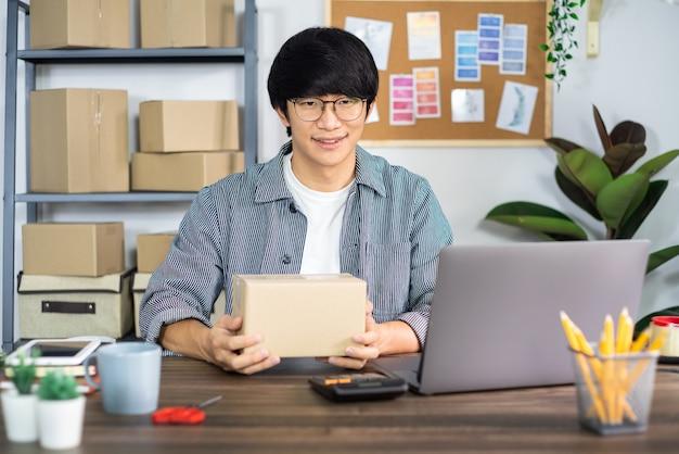 Uomo d'affari asiatico startup pmi imprenditore o freelance che lavora in una scatola di cartone prepara la scatola di consegna per il cliente, la vendita online, il commercio elettronico, l'imballaggio e il concetto di spedizione.