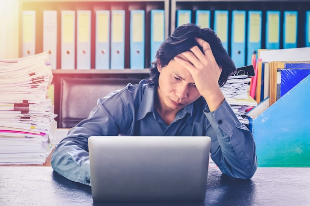 Sforzo o tensione asiatico dell'uomo di affari in ufficio con la sindrome di burnout allo scrittorio