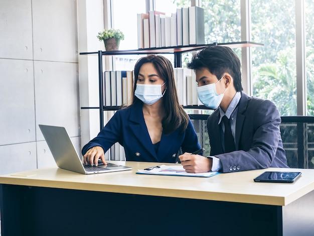 Uomo d'affari asiatico e donna che indossa tuta e maschere protettive utilizzando il computer sulla scrivania, incontrandosi e lavorando insieme in ufficio