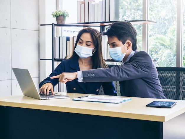 Uomo d'affari asiatico e donna che indossa tuta e maschere protettive utilizzando il computer sulla scrivania