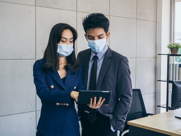 Uomo d'affari asiatico e donna che indossa tuta e maschere protettive utilizzando la tavoletta digitale