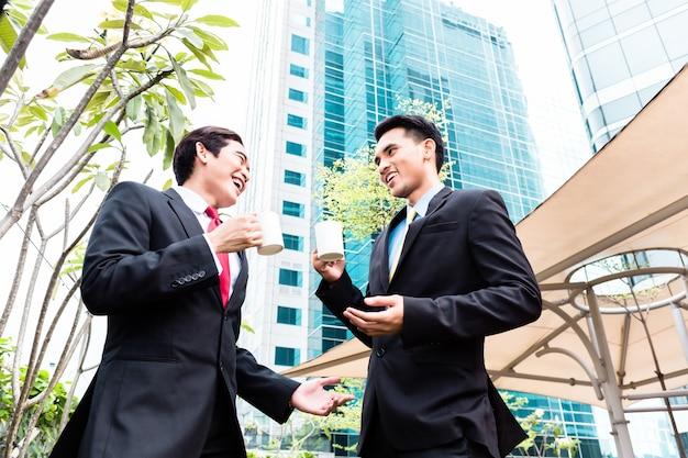 Uomini d'affari asiatici che hanno pausa caffè davanti all'edificio a torre