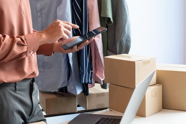 L'imprenditore asiatico che lavora a casa con la scatola di imballaggio del suo negozio online si prepara a consegnare prodotti ai clienti, concetto di stile di vita della generazione alfa.