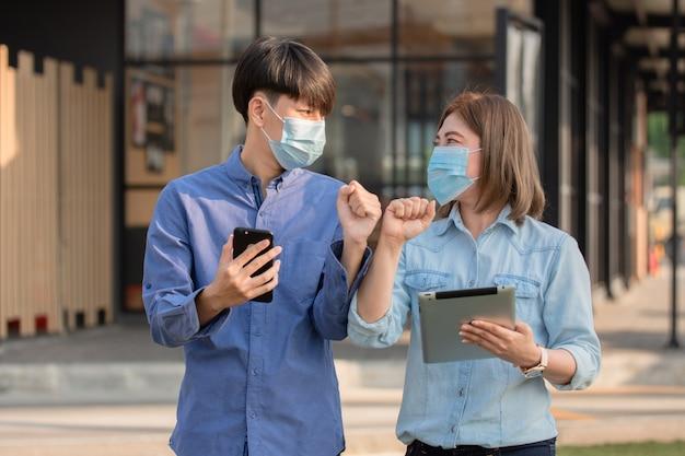 Gli uomini d'affari asiatici indossano una maschera per il viso che stringe la mano al gomito preventivo per il coronavirus covid19