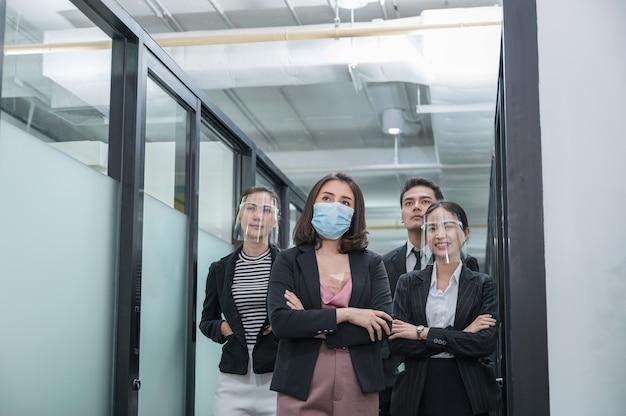 Asian business team fiducioso che indossa la maschera per il viso e la protezione per il viso in corridoio in un ufficio moderno
