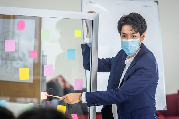 Asian business maschiaccio lesbica che indossa una maschera protettiva che presenta l'uso di post-it per condividere l'idea. concetto di brainstorming. nota adesiva sulla parete di vetro nella sala riunioni in ufficio, concetto di covid-19