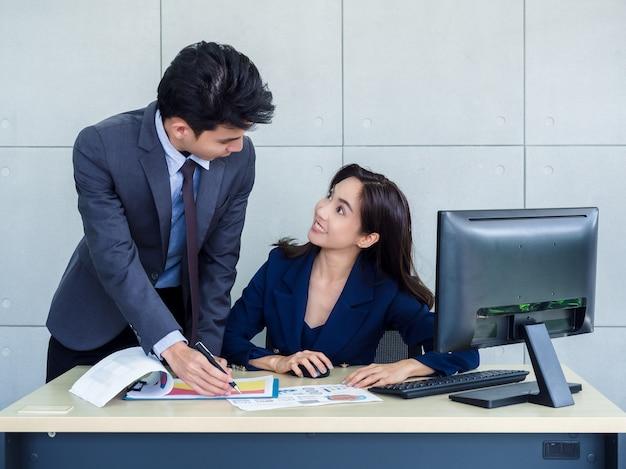 Donna d'affari asiatici e uomo d'affari che indossa tuta che lavorano insieme in ufficio Foto Premium