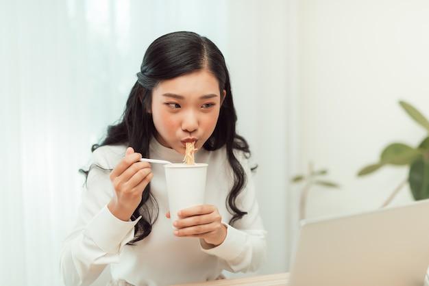 Donna asiatica di affari che mangia tagliatella alla scrivania per l'ora di pranzo
