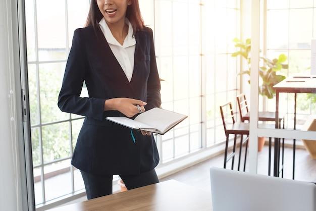 Donna asiatica di affari in vestito convenzionale che prende nota sul taccuino nella sala riunioni all'ufficio.