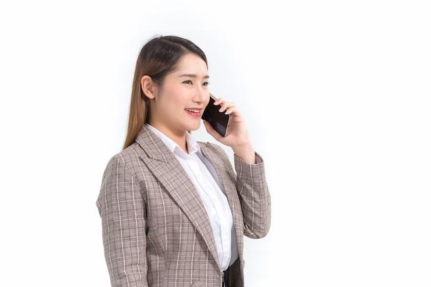 Una donna d'affari asiatica in abito formale con camicia bianca sta chiamando il telefono per controllare i dati