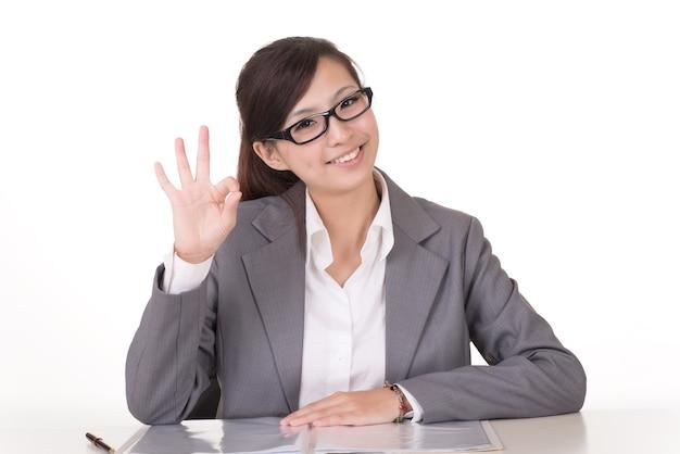 La donna asiatica di affari gli dà un gesto giusto, ritratto del primo piano su fondo bianco.