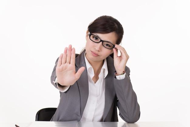 La donna asiatica di affari gli dà il segno rifiutato, ritratto del primo piano su fondo bianco.