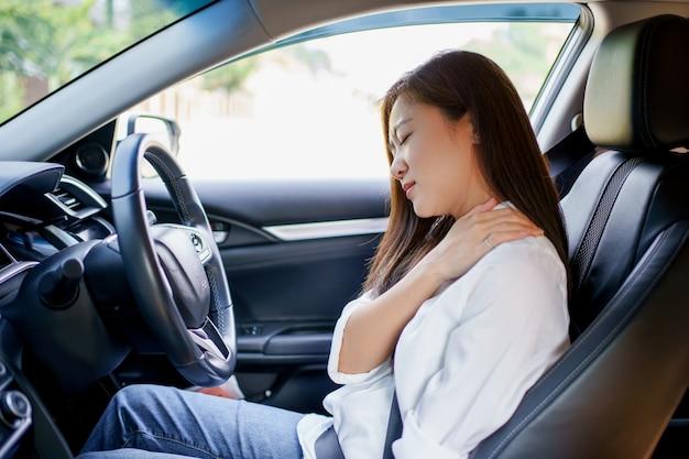 La donna asiatica di affari ha dolore alla spalla e al collo in macchina.