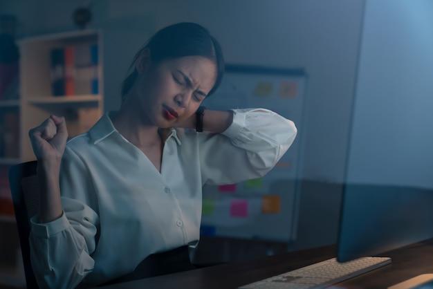 La donna asiatica di affari ha dolori al collo perché usa il computer e lavora a lungo la notte.