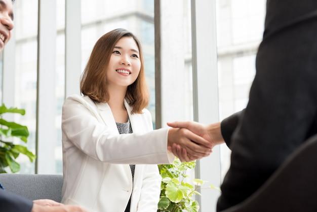 Donna asiatica di affari che fa stretta di mano con il cliente nel salotto dell'ufficio