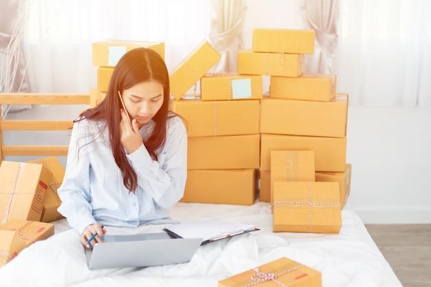 Il proprietario asiatico della donna di affari di pmi online che per mezzo del computer portatile riceve l'ordine dal cliente con la scatola del pacco