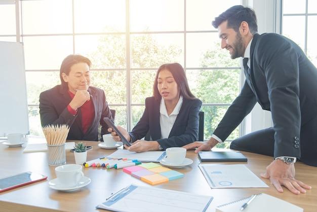 La donna asiatica di affari mostra la compressa all'uomo caucasico del collega nell'ufficio del lavoratore.