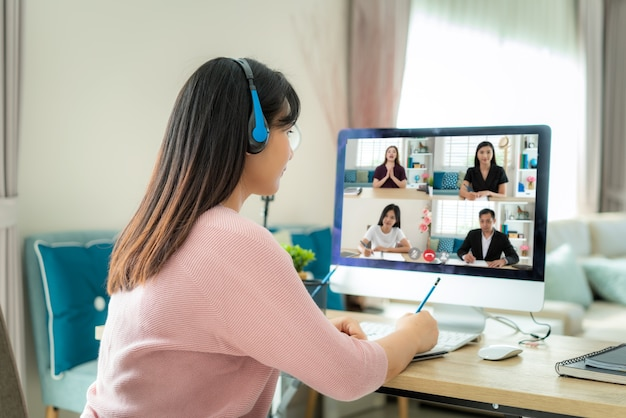 Donna asiatica di affari che parla con i suoi colleghi sul piano in videoconferenza.