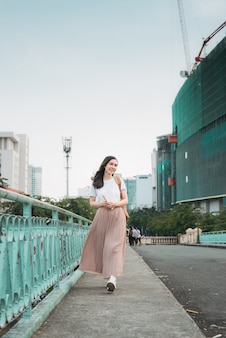 Asian business woman in viaggio, in piedi dal ponte di ringhiera, leggendo un libro sullo sfondo della città.