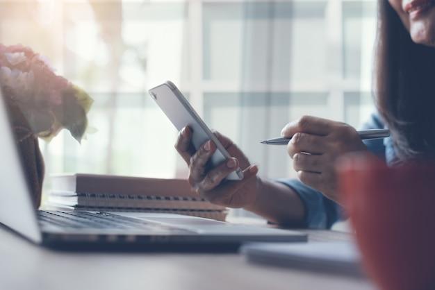 Donna d'affari asiatica che utilizza il telefono cellulare e lavora al computer portatile in ufficio