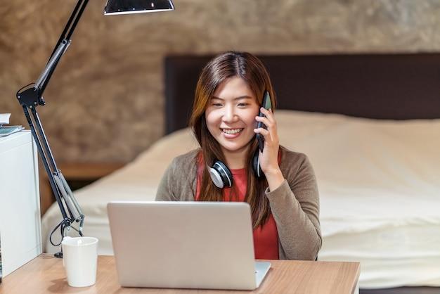 Donna d'affari asiatica che utilizza computer portatile tecnologico e lavora da casa in camera da letto