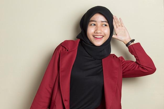 La donna asiatica di affari che porta l'hijab tiene la sua mano vicino al suo orecchio e ascolta
