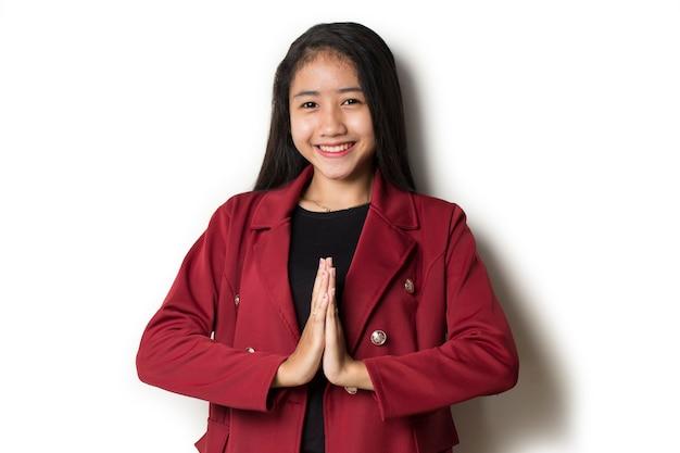 Donna asiatica di affari che accoglie favorevolmente gli ospiti gesto su bianco