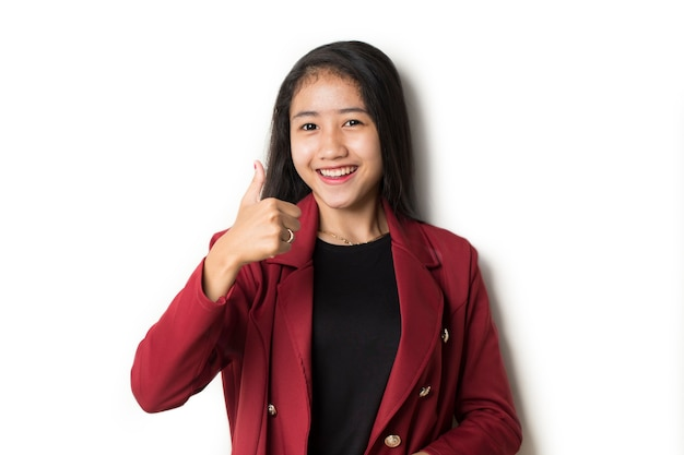 La donna asiatica di affari con i pollici in su della mano va bene