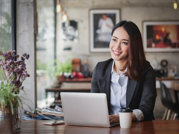 Donna asiatica di affari con il lavoro felice di successo di concetto di sorriso e del computer portatile