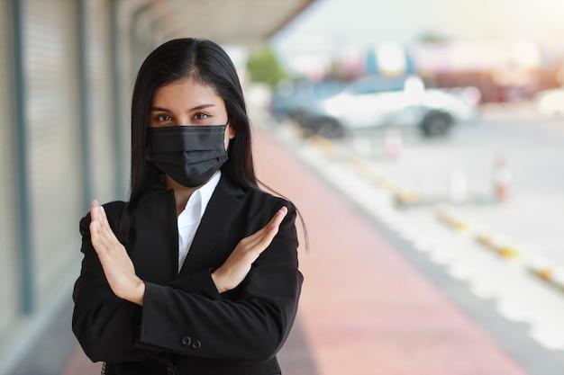 Donna d'affari asiatica con maschera protettiva che cammina sulla strada pubblica all'aperto e fa il gesto di smettere di incrociare le mani per fermare l'epidemia di virus corona.