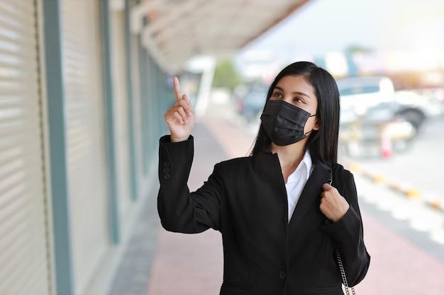 Donna d'affari asiatica con maschera protettiva per camminare sulla strada pubblica all'aperto e puntare qualcosa.