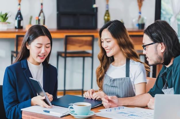 Donne asiatiche di affari che parlano del business plan con il proprietario della caffetteria e il barista in caffè.