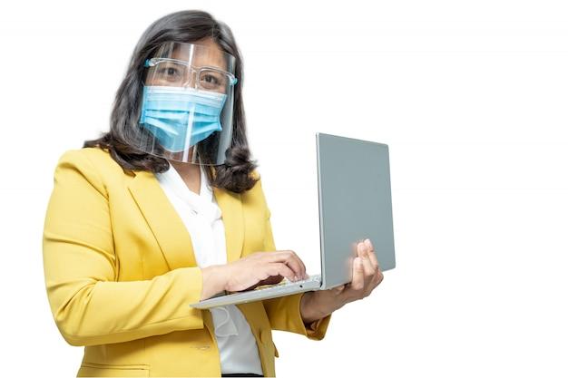 Le donne asiatiche di affari usano il taccuino del computer portatile che indossano la maschera e lo schermo facciale su fondo bianco con il percorso di ritaglio, nuovo normale per proteggere l'epidemia di covid-19 coronavirus dell'infezione di sicurezza all'ufficio.