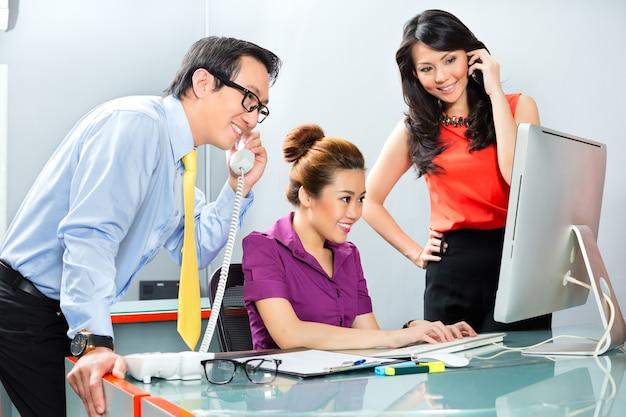 Lavoratori asiatici in un ufficio che lavorano insieme come una squadra per il successo in un progetto comune