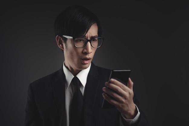 Uomo d'affari asiatico in abito nero preoccupato e guardando smart phone.