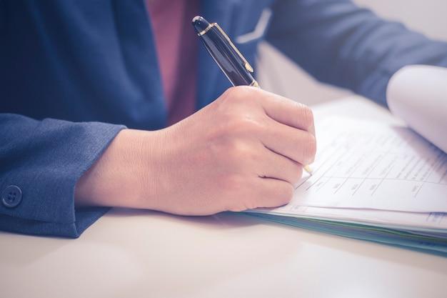 Uomo d'affari asiatico che controlla e firma nei rapporti di finanza di affari o primo piano di contabilità di fatturazione di affari.