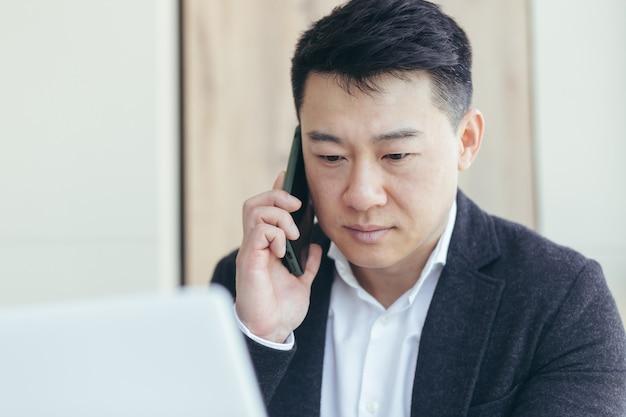 Ritratto ravvicinato di un uomo d'affari asiatico, di successo e di parlare seriamente al telefono, in giacca e cravatta