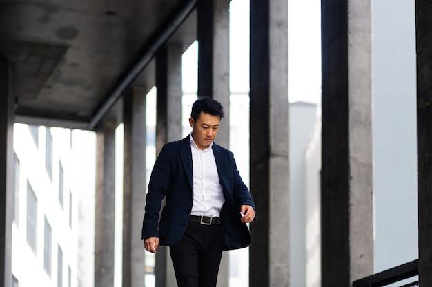 L'uomo d'affari asiatico va di fretta a fare una passeggiata vicino a un moderno centro di uffici
