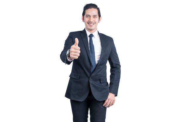 L'uomo d'affari asiatico passa le mani che mostrano i pollici aumenta il gesto isolato sopra la parete bianca