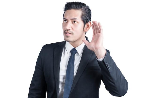 L'uomo d'affari asiatico sente qualcosa di isolato sopra il muro bianco
