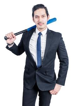 Uomo d'affari asiatico che tiene una mazza da baseball isolata sopra la parete bianca
