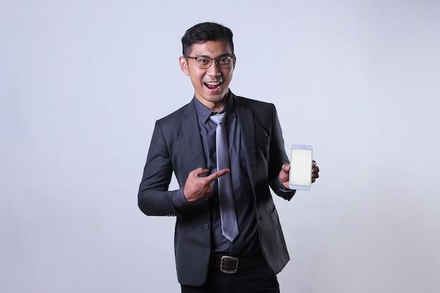 Un uomo d'affari asiatico tiene e indica uno smartphone con schermo vuoto con un'espressione eccitata