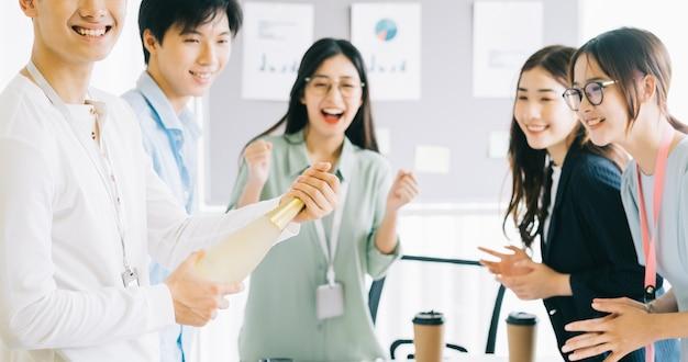 L'uomo d'affari asiatico sta aprendo lo champagne per festeggiare il nuovo anno con i membri del gruppo aziendale