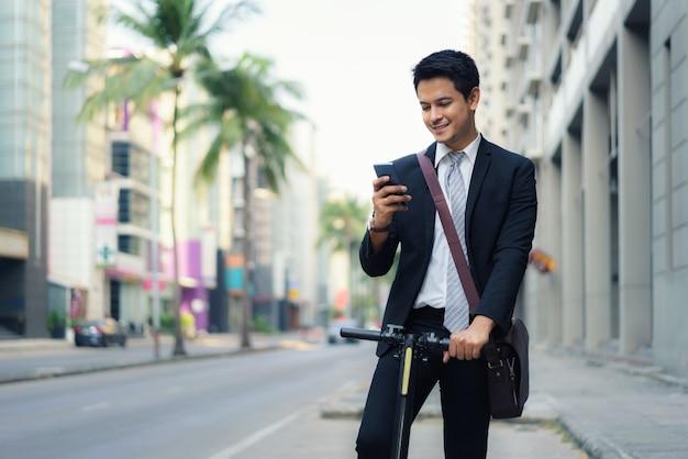 L'uomo d'affari asiatico sta guidando uno scooter elettrico e sta usando il suo telefono cellulare per aprire una mappa nell'applicazione per controllare i percorsi stradali della città per lavorare al mattino.