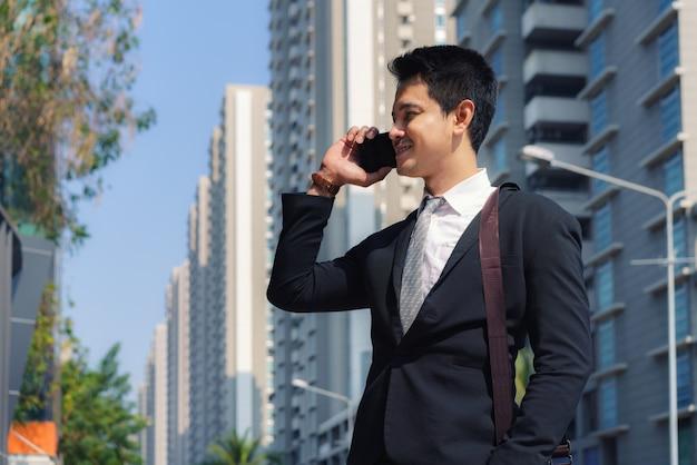 L'uomo d'affari asiatico è in piedi e parla con il suo collega al telefono per le strade della città durante il tuo tragitto mattutino.