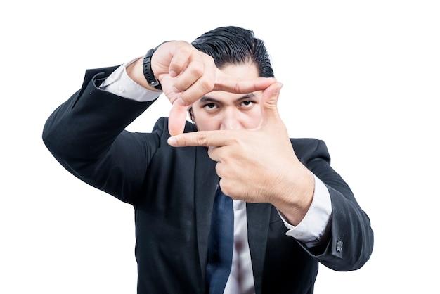 Uomo d'affari asiatico che fa struttura con le sue mani isolate sopra il muro bianco