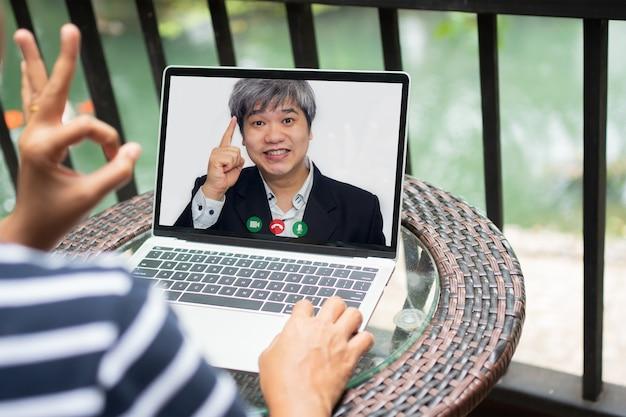 Uomo d'affari asiatico che fa una videochiamata al cliente