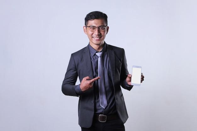 Un uomo d'affari asiatico che punta al telefono cellulare e sorride