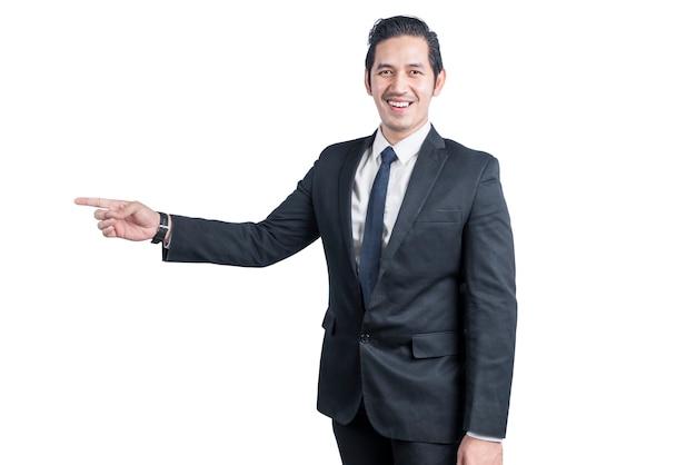 Uomo d'affari asiatico che indica qualcosa di isolato sul muro bianco