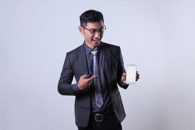 Un uomo d'affari asiatico punta il dito su uno smartphone con schermo vuoto con un'espressione rassicurante